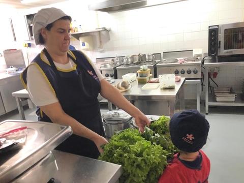 Entrega dos legumes colhidos na cozinha